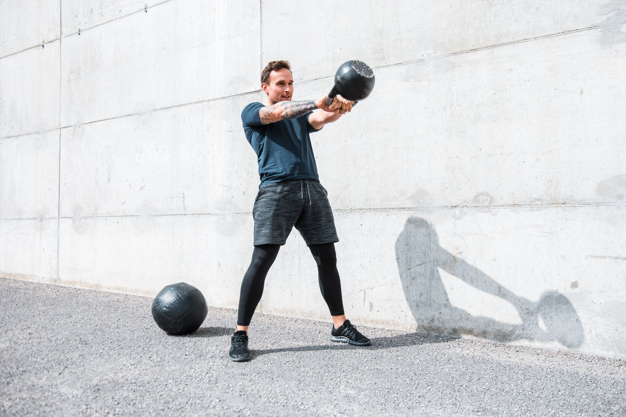 man-exercising-with-a-kettlebell-outdoors-royalty-free-image-955272210-1547755193